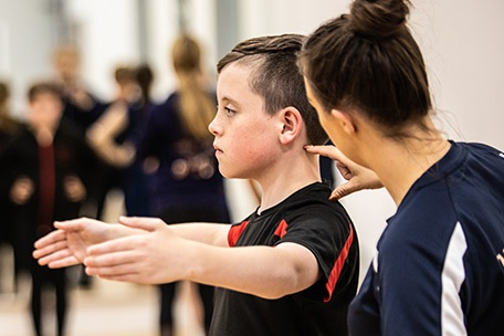 Dance Crazy Studios instructor adjusting young boy's posture